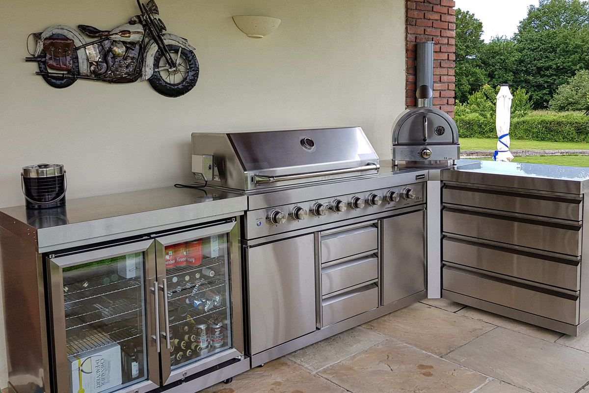 Corner shaped outdoor kitchen in stainless steel and a small pizza oven